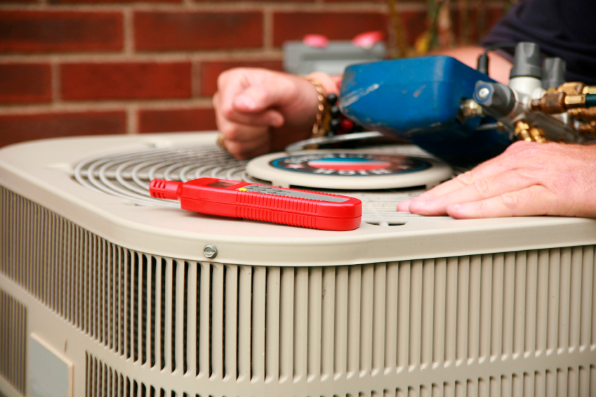 close-up of hands on outdoor heating and ac unit making repairs